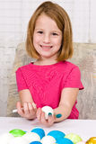 Young girl coloring Easter Eggs. A young girl holds a white crayon and a hard boiled egg, in the process of coloring Easter Eggs. She plans on writing on the egg Stock Images
