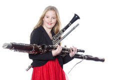 Young girl holds woodwind instruments in studio Royalty Free Stock Photo
