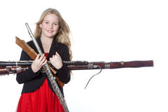 Young girl holds woodwind instruments in studio. Young blond girl holds woodwind instruments in studio against white background Stock Photography