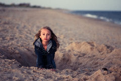 Young girl in hole on beach Stock Photo