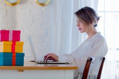 Girl with gift boxes and laptop computer royalty free stock image
