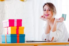 Girl with holiday gifts and laptop computer holding a credit card stock photography