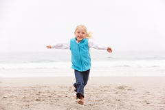 Young Girl On Holiday Running Along Winter Beach. Smiling At Camera Royalty Free Stock Photos