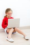 Young girl at home with laptop. Stock Images