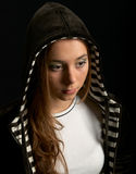 Young girl in hood. Against a dark background Royalty Free Stock Photos