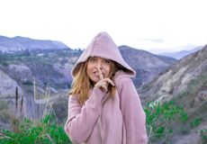 A young girl in a hood presses her finger to her lips and mysteriously looks. royalty free stock photo