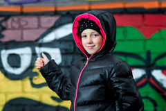 Young girl in hooded vest thumbing to the graffiti Stock Images