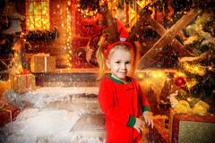 Young girl with horns. Pretty three year old girl is standing near his house decorated for Christmas in a deer suit with horns on the head. Merry Christmas and royalty free stock photography