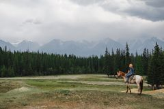 Young girl on horse in mountains. Young girl with red head riding by horse. Beautiful green forest and big mountains on the background stock image