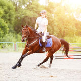 Young girl on horse at show jumping competition. Young rider girl on bay horse galloping on her course at show jumping competition Stock Photos