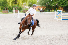 Young girl on horse at show jumping competition. Young rider girl on bay horse galloping on her course at show jumping competition Stock Images