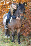 Young girl on horseback stroking a horse. Autumnal background Royalty Free Stock Photos
