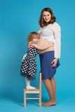 Young girl hug pregnant mother Stock Photos