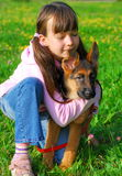 Young Girl Hugging Her Dog. Young girl with eyes closed kneeling in a field, hugging her young German Shepherd sitting beside her Stock Photography