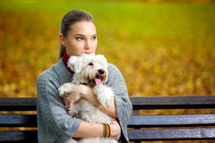 Young  girl hugging  her dog. In park Royalty Free Stock Image