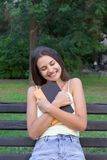 Young girl is hugging her favourite textbook in the park.  royalty free stock image