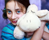 A young girl  hugging her toy lamb Royalty Free Stock Images