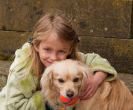 Young girl hugging a little dog with a ball. Young girl hugging a little dog that has a ball in his mouth Stock Photo