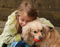 Young girl hugging a little dog with ball Stock Photography