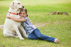 Young girl hugging pet dog at park Royalty Free Stock Photos
