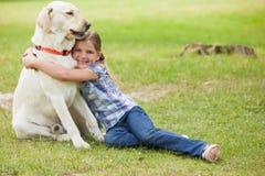 Young girl hugging pet dog at park Royalty Free Stock Photos