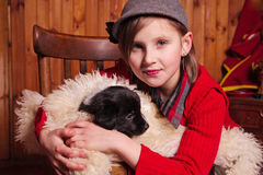 Young girl hugging a puppy wrapped in a sheepskin. Farm. Stock Photography