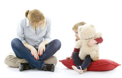 Young girl hugging teddy bear with mum Royalty Free Stock Images