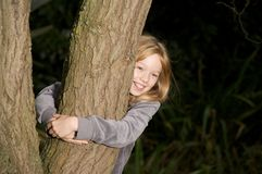 Young girl hugging a tree. Young girl smiling and hugging a tree Stock Photo
