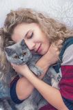 Young girl hugs Scottish cat Royalty Free Stock Image