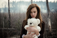 Young girl hugs a teddy bear on the background of burnt forest Stock Photos