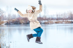 Young girl hung in jump over winter pond Royalty Free Stock Photography