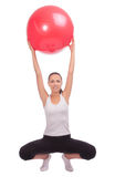 Young girl on hunkers and having fitball lifted up Stock Image