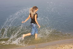 Young  girl hurries on water Stock Images