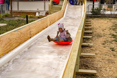Young Girl on the Ice Slide Royalty Free Stock Photos