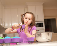A young girl ices cupcakes Stock Photos