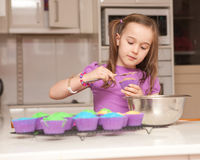 A young girl ices muffins Royalty Free Stock Photo