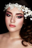 A young girl in the image of a bride with a floral wreath on her head and curls. A beautiful model with a bright makeup and perfec Stock Photos
