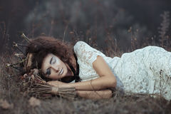 Young girl in the image of a bride lying on the ground Royalty Free Stock Photo