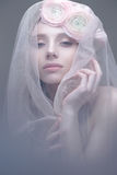 A young girl in the image of a bride with a veil on her face. Beautiful model with a wreath of flowers on her head Stock Photo