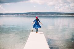 Free Young Girl In A Floating Dress Standing At The End Of The Pier In Front Of A Calm Sea Royalty Free Stock Photo - 176951475