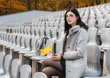 Young Girl In A Gray Coat Sits On A Seat Of An Empty Stadium Royalty Free Stock Photos