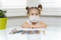 Free Young Girl In A White T-shirt Draws Pencils At The Window In Mask Stock Photography - 181248392