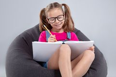 Young Girl In Glasses Doing Homework On A Gray Bean Bag Royalty Free Stock Photos