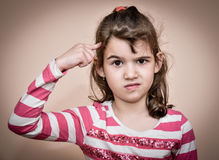 Young girl with the index finger on her head. Showing that you are crazy Royalty Free Stock Images
