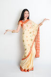 Young girl in Indian sari dress welcoming. Portrait of young mixed race Indian Chinese woman in traditional sari dress dancing, on plain background royalty free stock photos