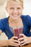 Young girl indoors drinking juice Royalty Free Stock Images