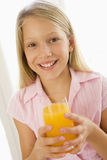 Young girl indoors drinking orange juice smiling Royalty Free Stock Photo