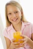 Young girl indoors drinking orange juice smiling Royalty Free Stock Photo
