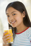 Young girl indoors drinking orange juice smiling Stock Images