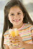 Young girl indoors drinking orange juice smiling Stock Photo